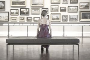 Woman sitting on a bench, looking at paintings in museum