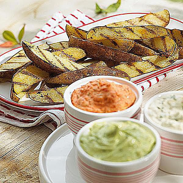A plate of grilled potato dippers with sauces