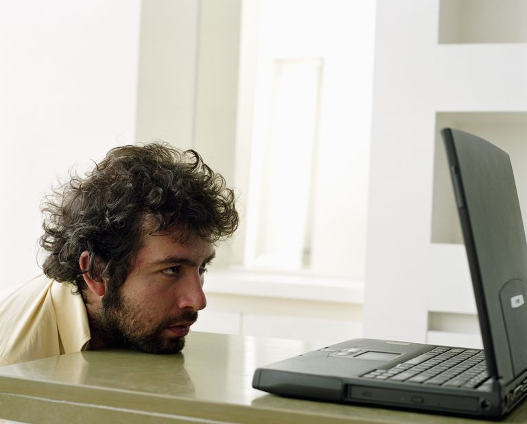 Young man staring at open laptop, side view