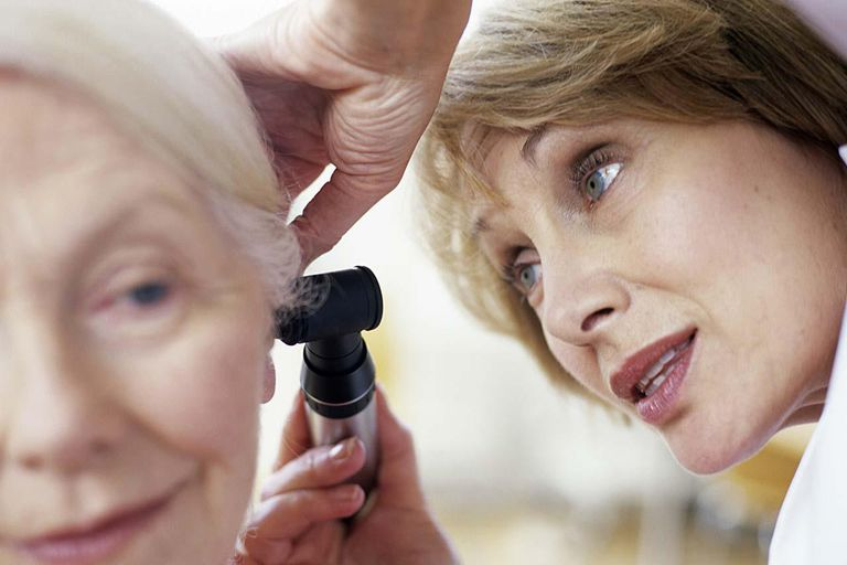 General practice doctor examining old woman's ear using otoscope