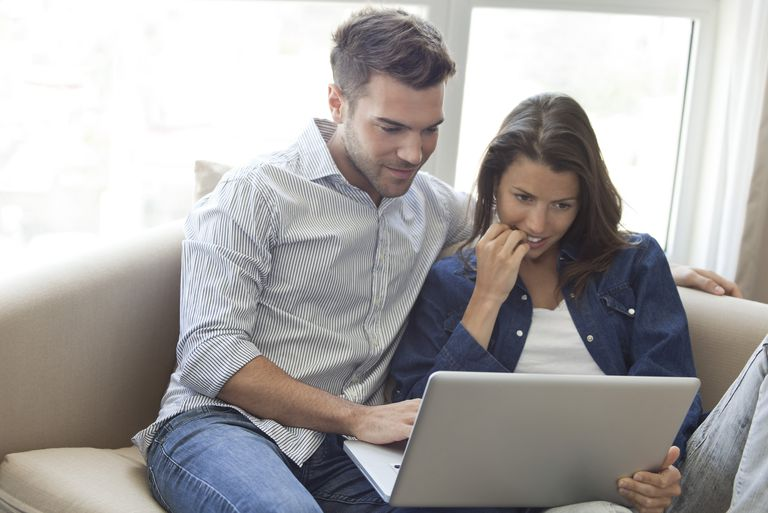 Couple using laptop computer together at home