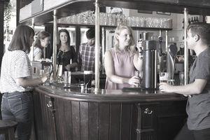 Female bartender pulling a pint