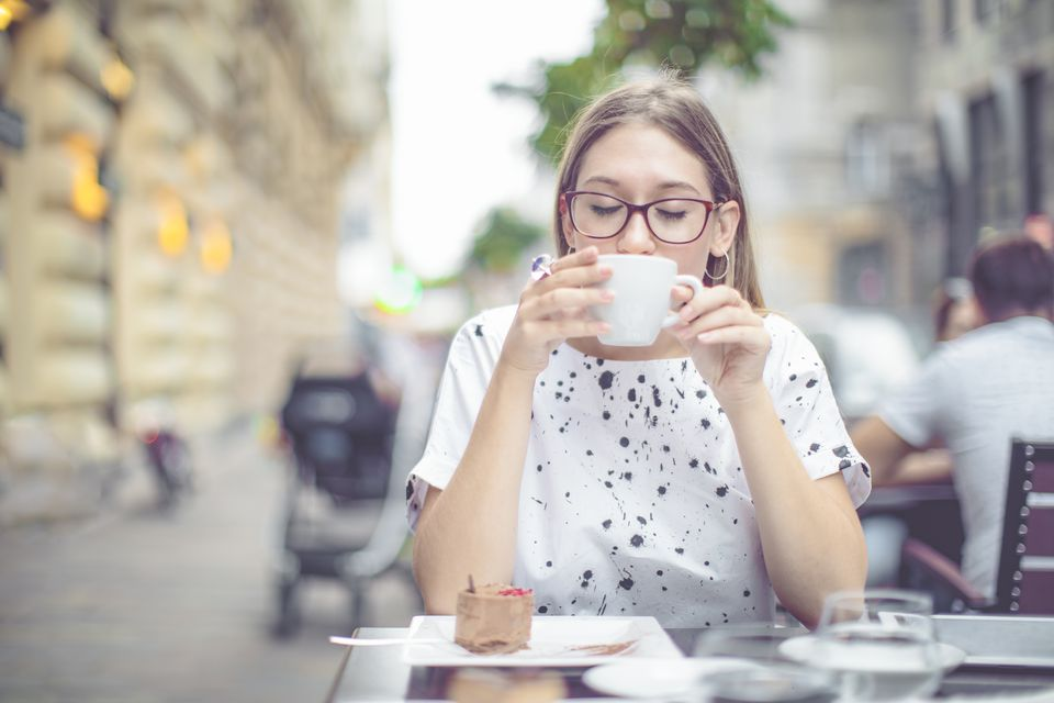 A young woman drinking coffee outside