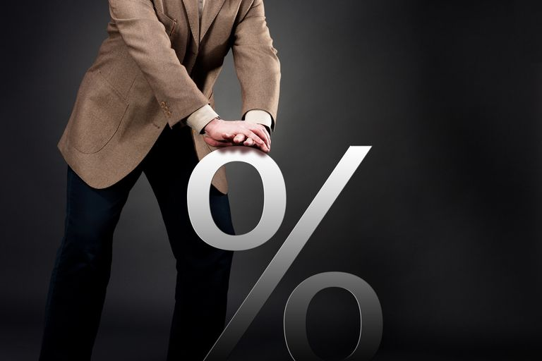 Man in Suit Pushing Percent Sign Down