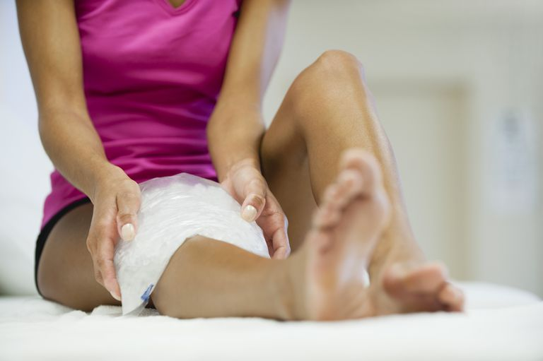 woman putting ice on sprained knee