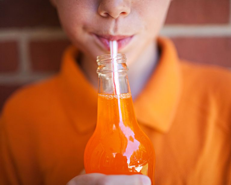 Boy drinking orange soda