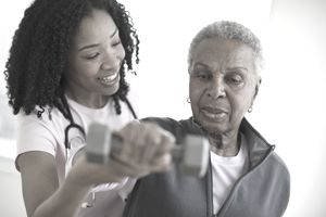 Nurse helping woman exercise with dumbbell