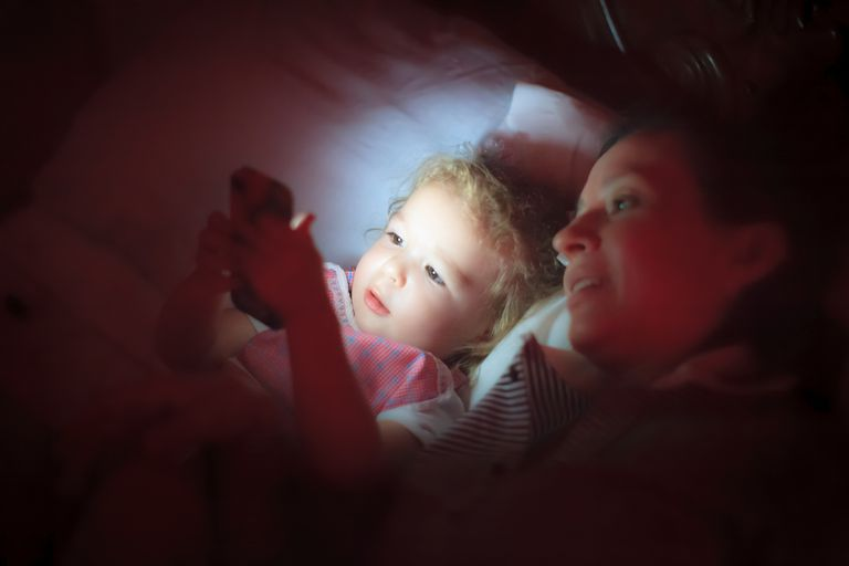 child and mother playing on cell phone in bed at night
