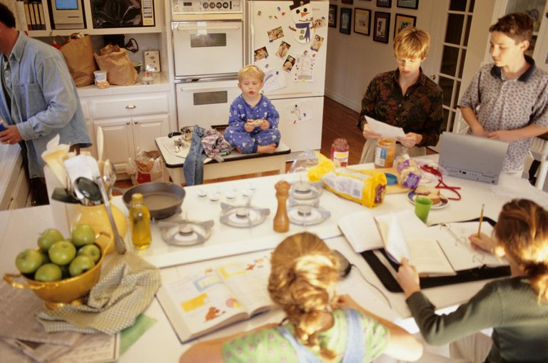 Large family in kitchen in morning, daughters (8-9) doing school work, elevated view