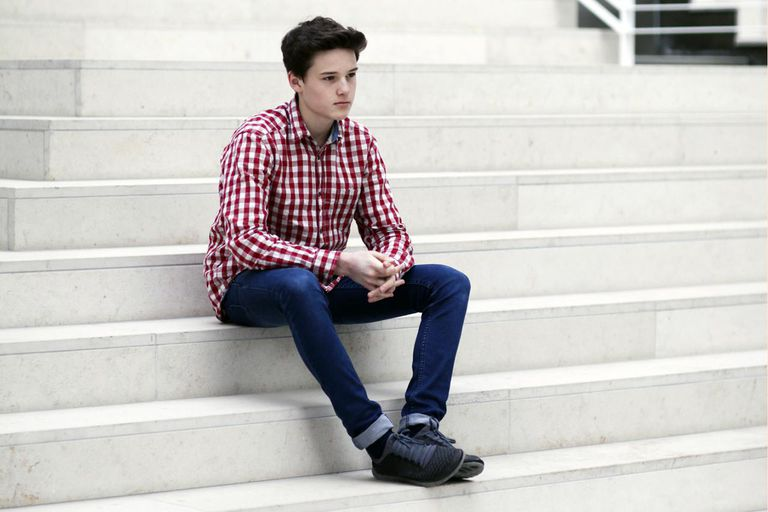 Teenage boy sitting on steps thinking about body appearance