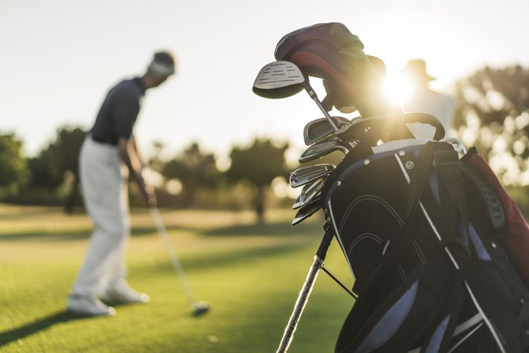 Close-up of golf bag with people in background