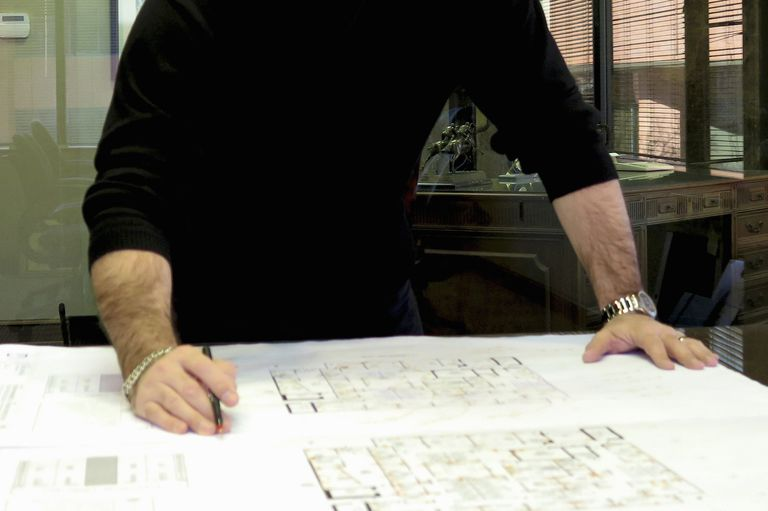 Cropped photo of male architect's arms and hands on a large blueprint