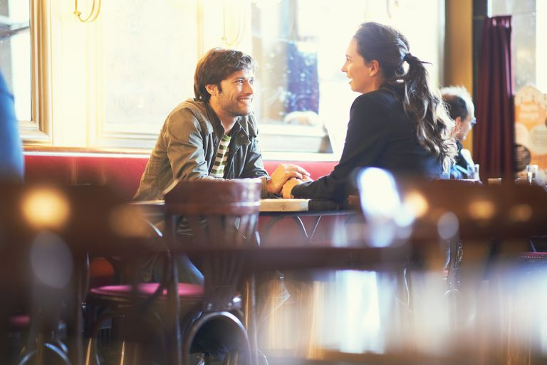Couple holding hands in cafe bar