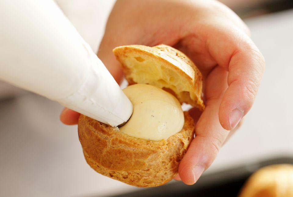 Piping vanilla pastry cream into a cream puff