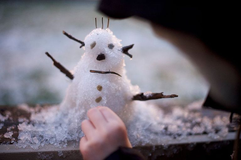 child making a tiny snowman on a windowsill