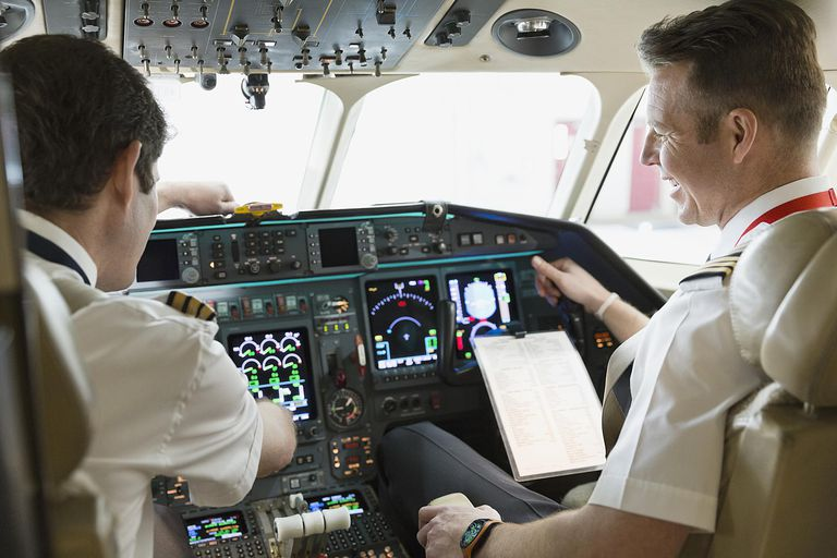 Pilot and co-pilot checking instruments in cockpit of plane