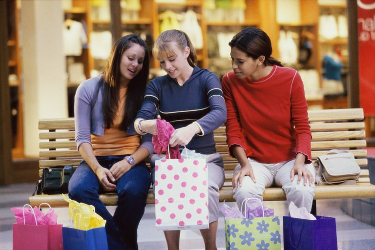 Three teenage girls looking at clothes in shopping bags