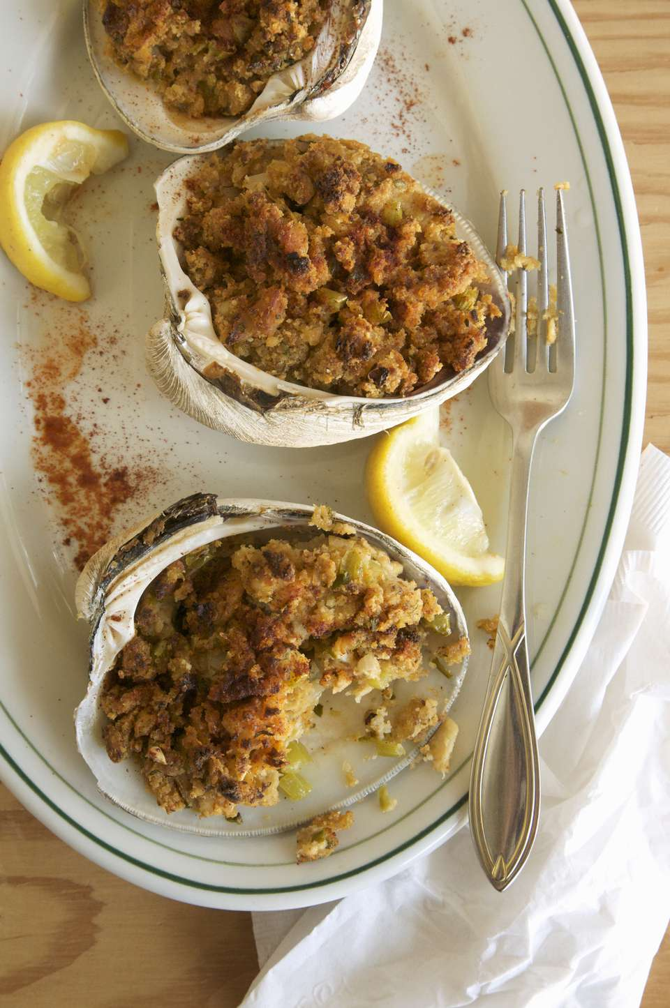 Stuffed clams with lemon garnish on plate, close up