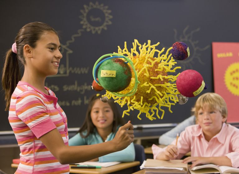 girl showing science project to class