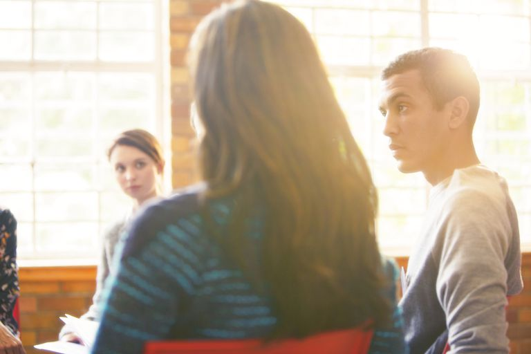 Men and women sitting in a circle talking