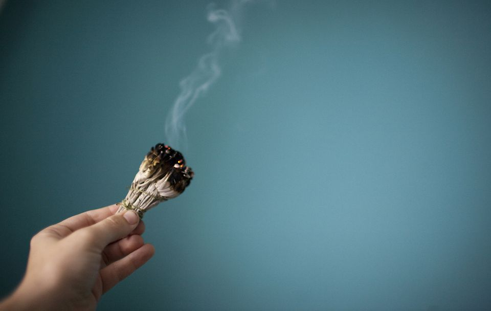 A hand holding a smoking sage smudge stick for a smudging ceremony in an empty blue space.