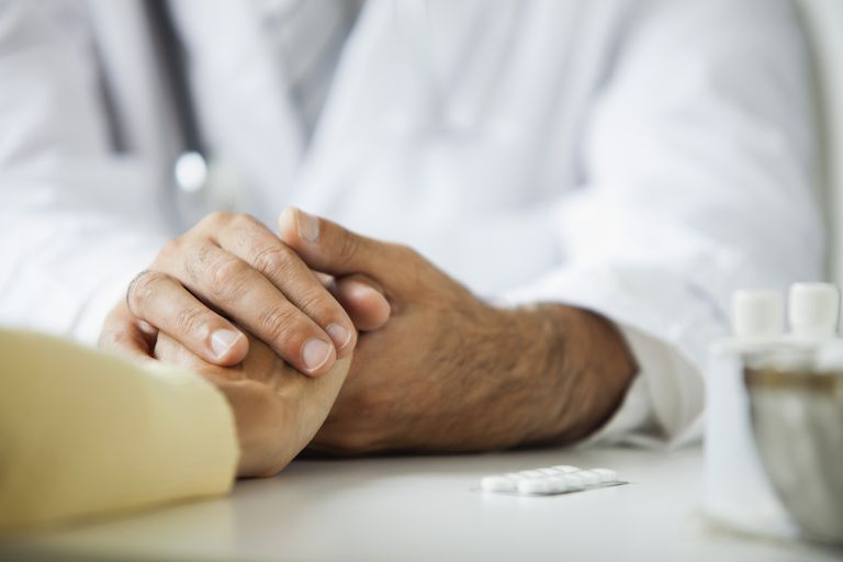 Doctor comforting patient during consultation