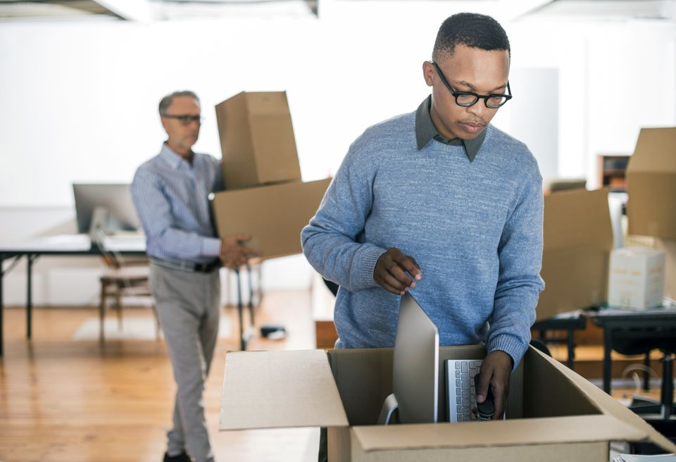 African American man wearing glasses packs a box to move his office