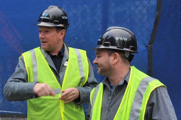 Photo of two men in hard hats and bright yellow-green reflective safety vests on a work site.
