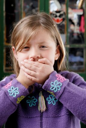 young girl covering her mouth as if she's said something she shouldn't have