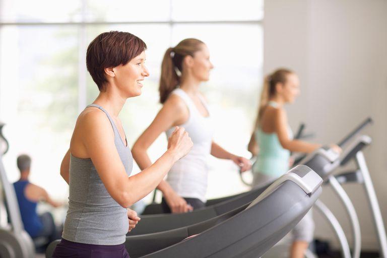 Portrait of smiling women running on treadmills in gymnasium