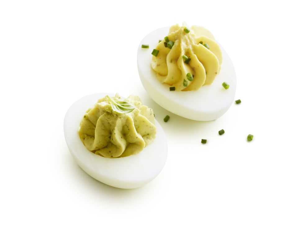 Two deviled eggs garnished on white