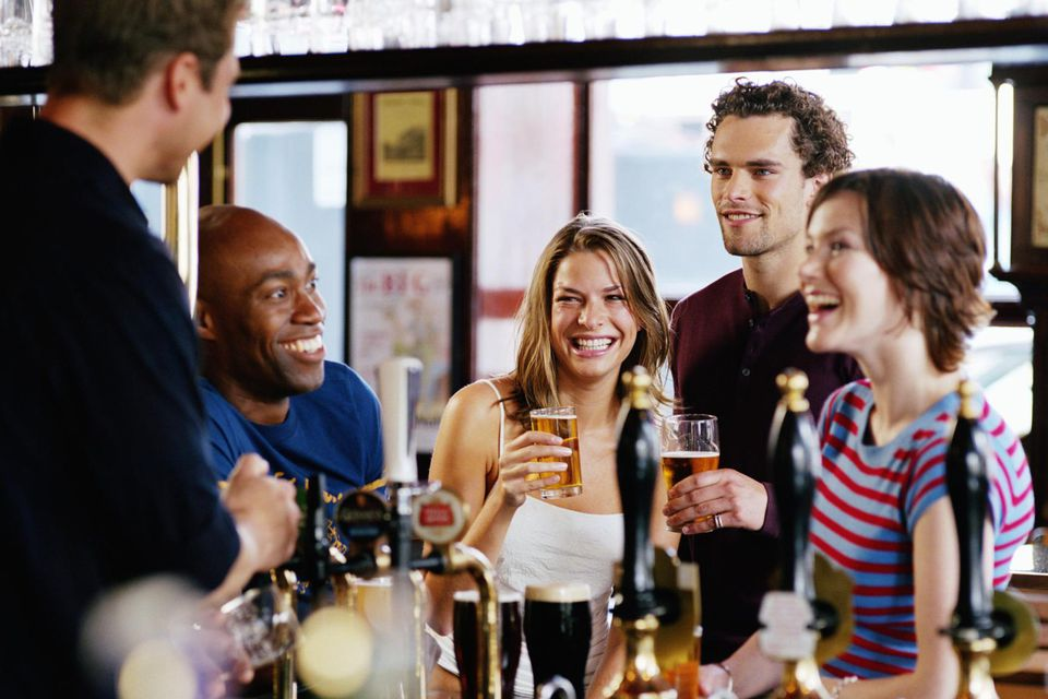 Group of friends at bar talking to barman, smiling