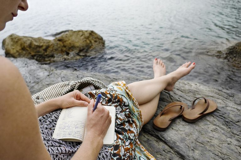 Woman writing in journal on seaside of Italy.