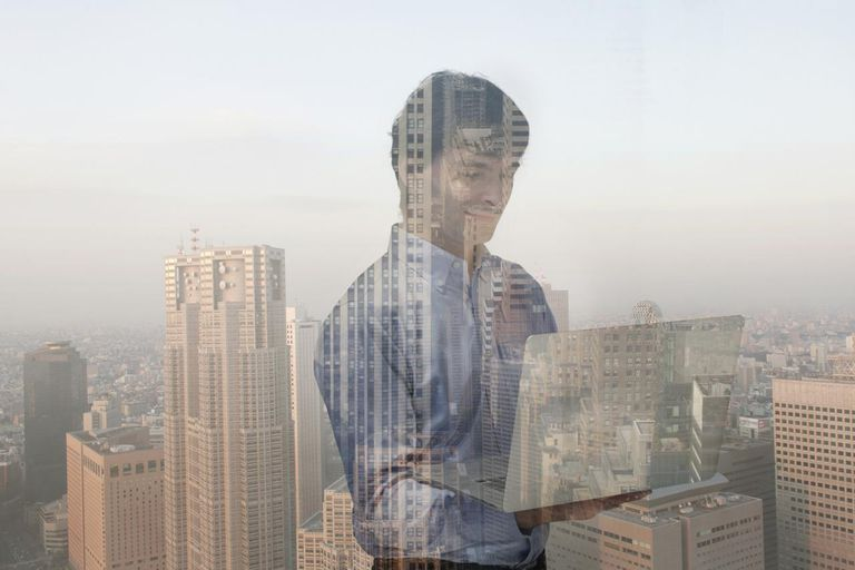 Composite of man using laptop and cityscape