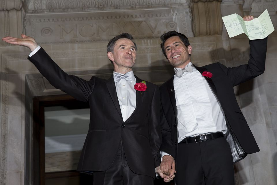 grooms celebrate with wedding certificate