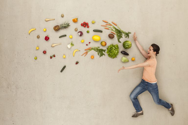 Artistic display of a woman catching a bunch of fruits and vegetables