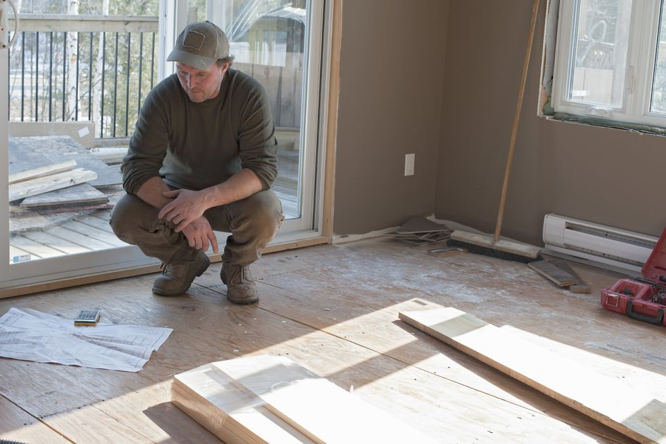 Contractor Looking At Blue Prints In A New Hom