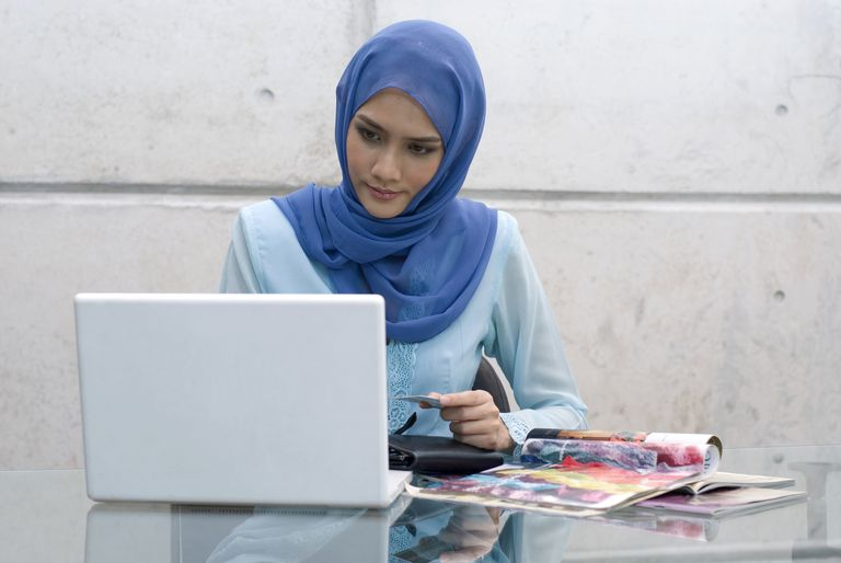 Malaysian Muslim woman using credit card and laptop