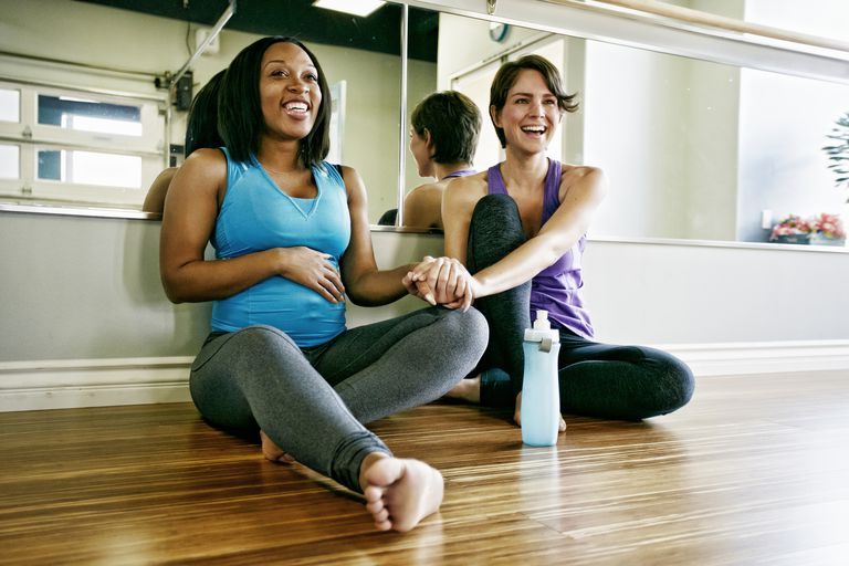 Women holding hands in yoga studio