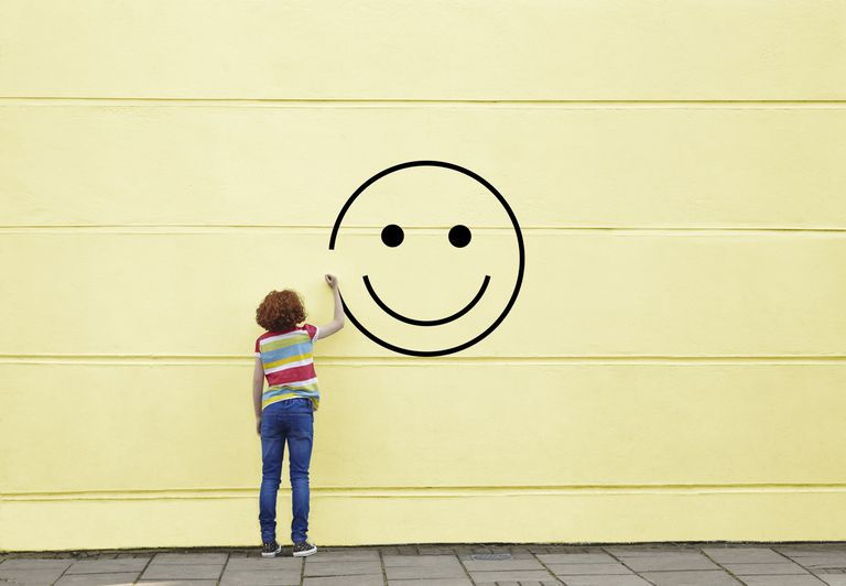Woman drawing a happy face on a wall.