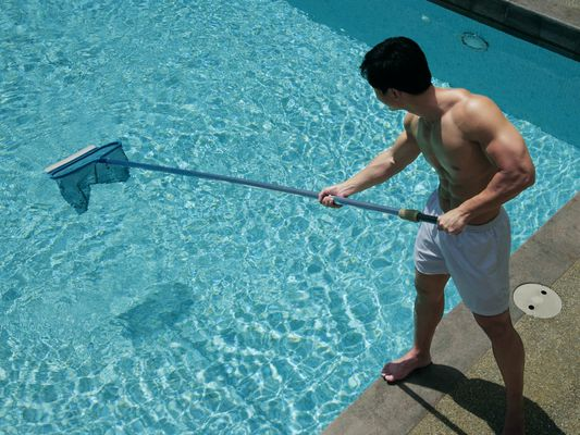 Young man cleaning pool