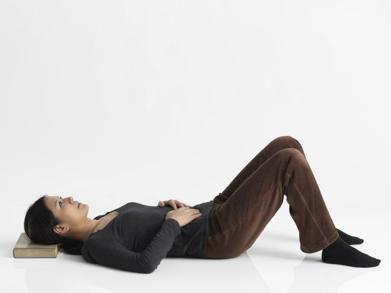 Woman laying on wooden floor in supine position, head resting on book