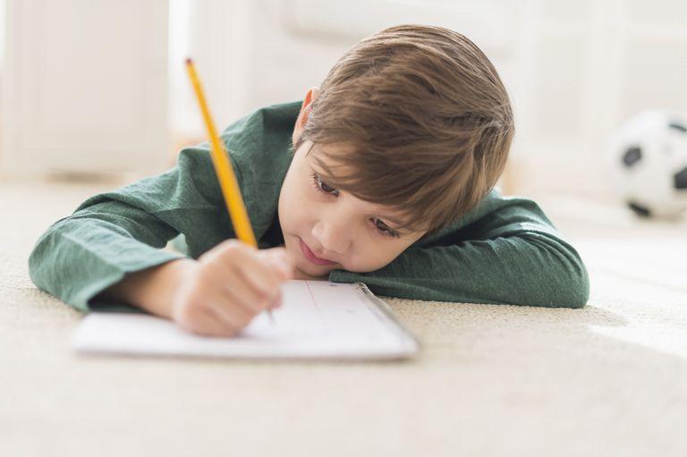 Hispanic boy doing homework on floor
