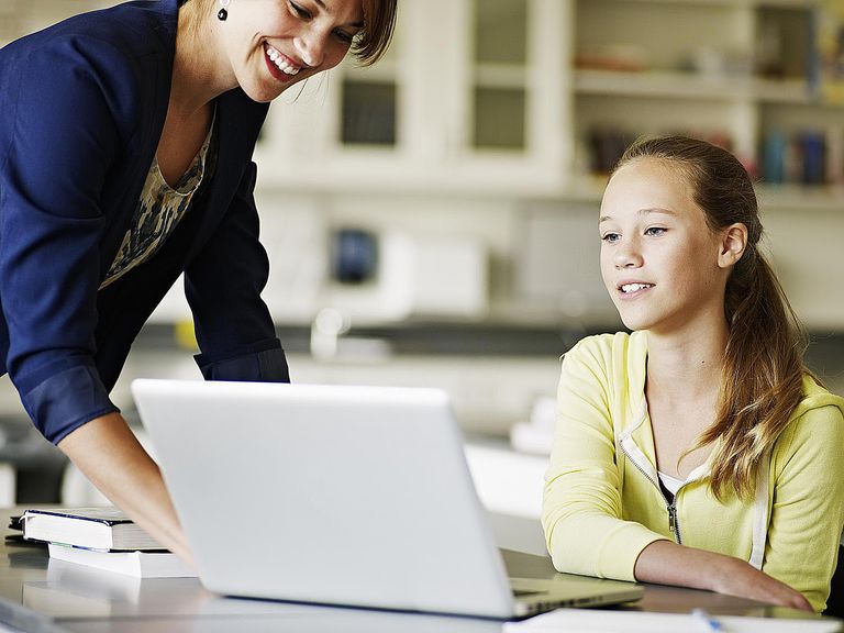 Substitute Teacher helping young student working on laptop