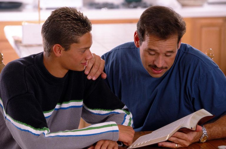 father reading Bible to son