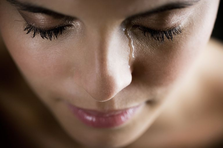 Woman with eyes closed and a tear falling down her cheek