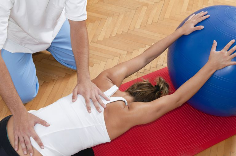 physical therapist working on woman's back