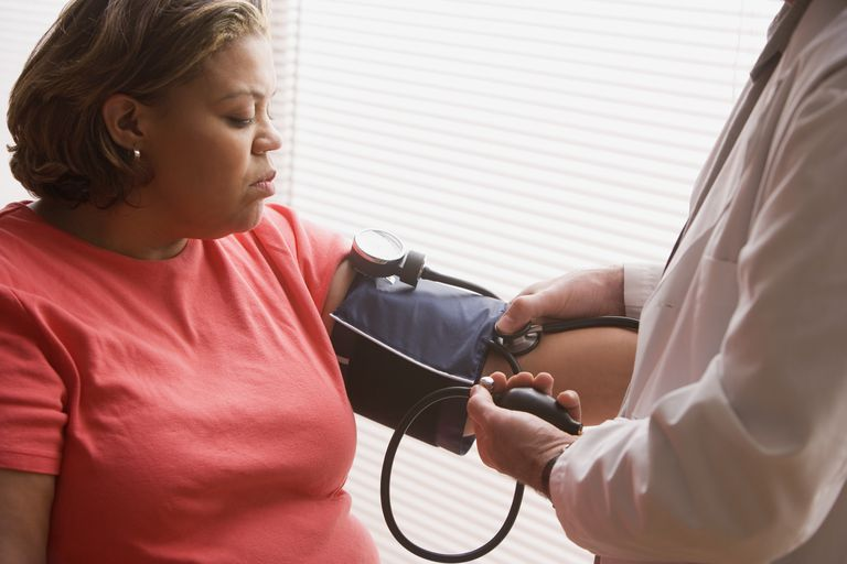 Middle-aged overweight Hispanic woman having her blood pressure checked