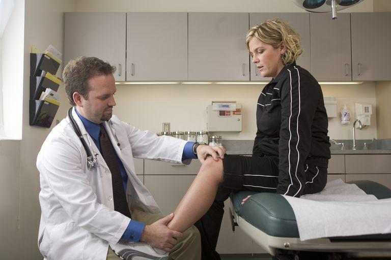 Doctor examining female patient's leg