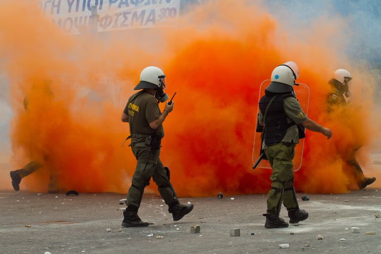 Police in front of orange-colored smoke